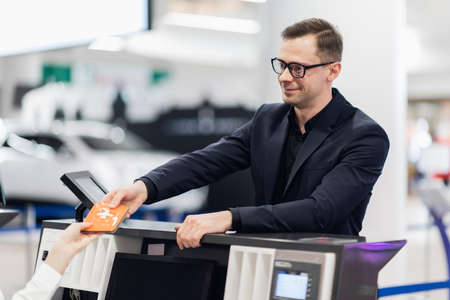 Business trip. Handsome young businessman in suit holding his passport and talking to woman at airline check in counter in the airport Zdjęcie Seryjne