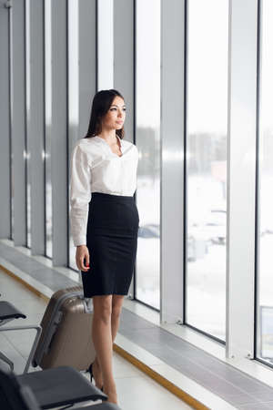 Portrait of a young business woman in smart clothes walking along hotel lobby with her suitcase
