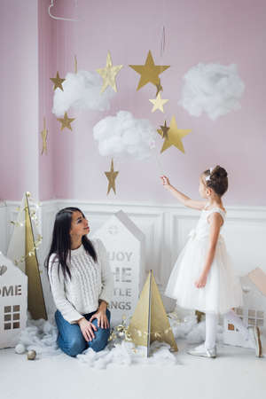 Beautiful mom with daughter fairy pressed against each other on magic background decoration. Playing the princesses and fairies. Mothers love, happiness and fairy tale concept.