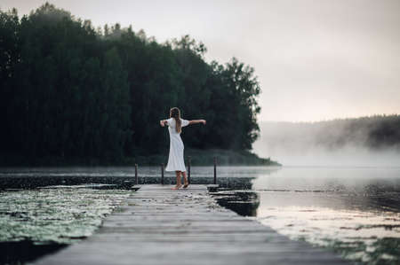 Back view of young woman in white dress standing alone on footbridge and staring at lake. Foggy chilly morning with a mist over water.