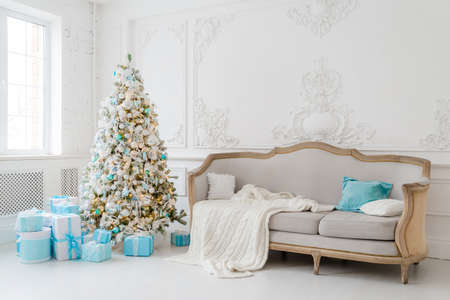 Stylish Christmas interior with an elegant sofa. Comfort home. Presents gifts underneath the tree in living room