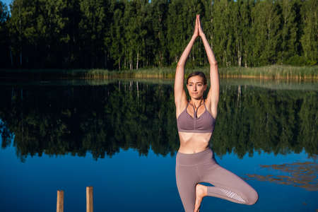 Healthy woman practicing yoga on the lake at sunrise enjoying positive energies from nature