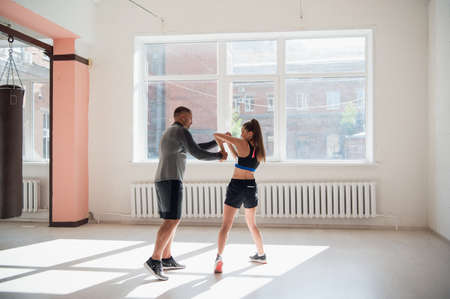 The first training of a novice girl fighter in kickboxing, the coach shows the blows