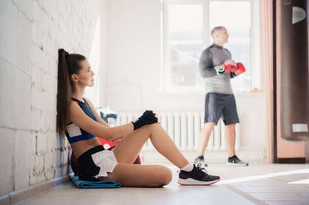A professional womens boxing and kickboxing coach rests on the floor against a white brick wall
