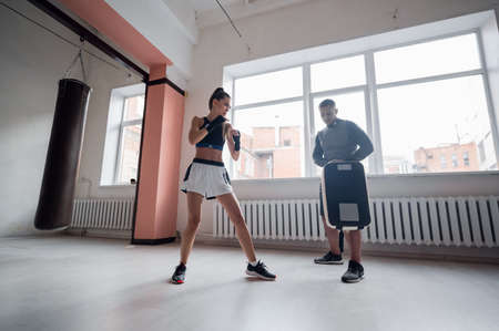 Training fight of male and female kickboxers. Practicing kicks and strikes on the boxing paw. Working in pairs 免版税图像