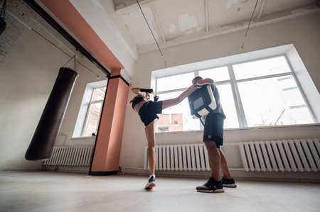 A young female athlete in good physical shape conducts kickboxing training under the supervision of an experienced male coach