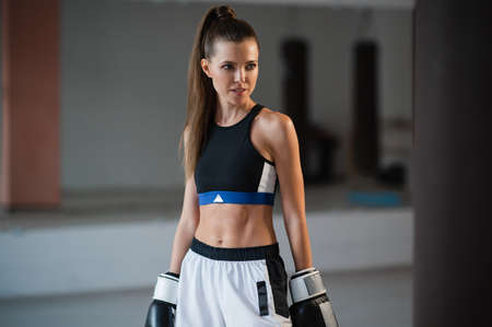 Portrait of a young attractive girl boxer in the gym wearing gloves next to a punching bag