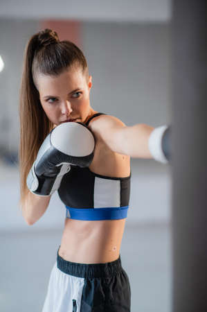 A girl in sports clothes is engaged in boxing and works out a punch with her hand on a punching bag 免版税图像