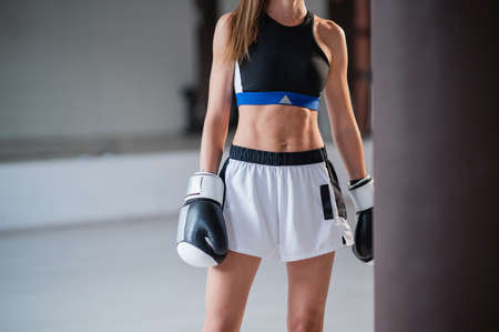 The body of a young slender athlete kickboxer without a face with a pumped up press in a sports uniform and gloves in the gym with a punching bag Standard-Bild