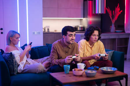 Two male friends excited to play video games at home while a girl sitting with them on a couch and using mobile smart phone. 免版税图像