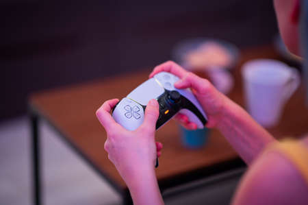 Close view of a girl gamers hands playing video game on Playstation 5 gaming console using DualSense PS5 joystick. Moscow - November 28 2020.