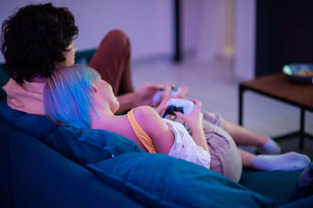 Smiling couple holding gamepads playing video game at home. Young people spending time together during self isolation on pandemic.