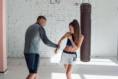 In the boxing hall, an experienced trainer teaches a young girl the correct stance