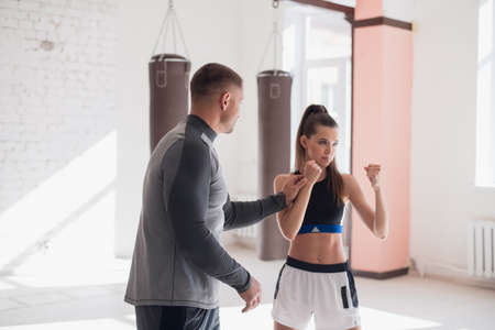 An experienced trainer puts the technique of blows to a young girl in the boxing hall