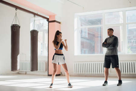 In a spacious loft, a male trainer and his female mentee conduct a boxing training session