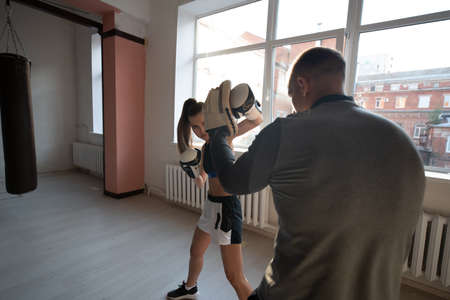 A man and a woman sparring partners train in the fighters training hall in boxing gloves with paws