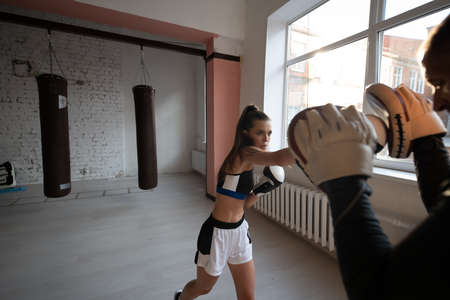 A young girl conducts kickboxing training and practices paw strikes with a professional boxer 免版税图像