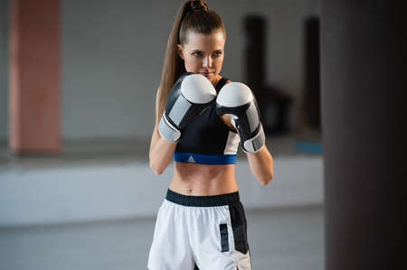 The girl is preparing for a boxing competition and trains punches on a punching bag in a spacious gym