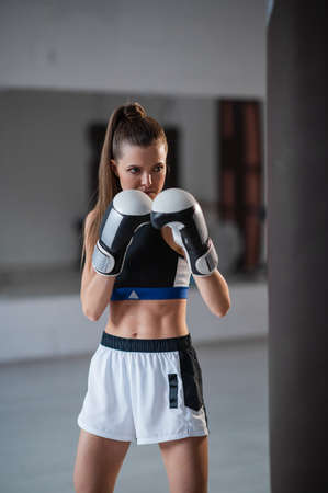 A pretty kickboxer girl is preparing for competitions in the boxing hall, practicing the technique of punches on a punching bag