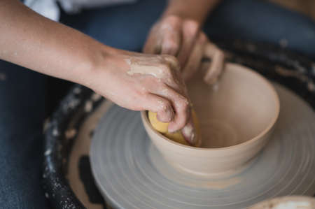 Potter makes the clay product with pottery modeling tools on the potters wheel.