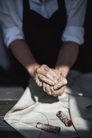 The potters woman hands are shaping a cup from a clay. The process of creating pottery. The master ceramist works in his studio. Close-up, only hands. Crockery from clay own hand
