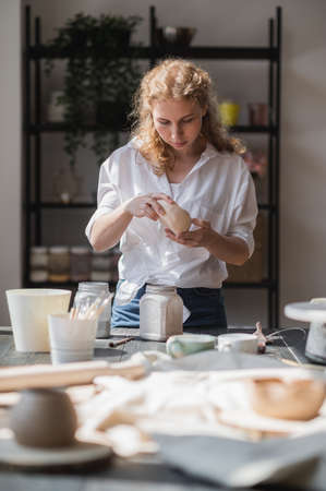Girl draws on a clay bowl. Female potter works in her studio glazing ceramic pot.
