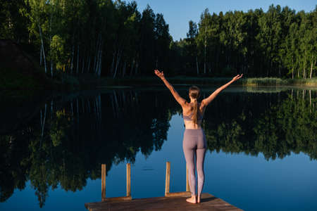 Young woman on wooden pier above forest lake scenery, folds her arms in a namaste gesture. Woman arms outstretched in nature.