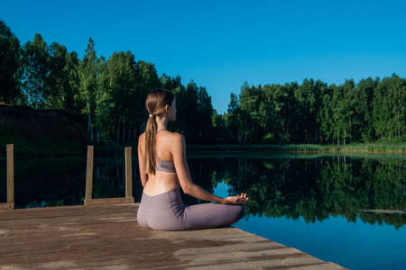 Young attractive girl practices yoga by the lake at sunset. Sitting in lotus position by the water.