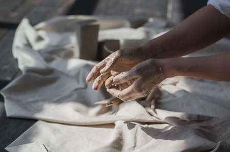 Womans hands wet and dirty after working with clay in a pottery studio