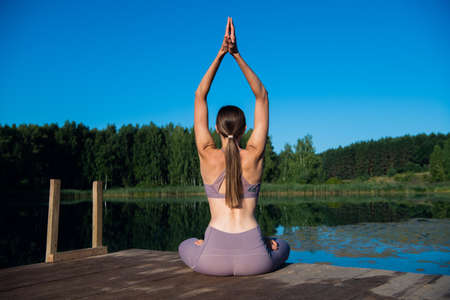 Beautiful young woman performing a spiritual yoga pose on a forest lake at sunny day, sunrise zen wellness