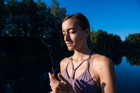 Woman doing yoga and meditating in a sunrise outdoors, holding aroma stick in her hands, palms in namaste gesture. 免版税图像