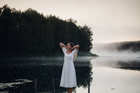 Young woman breathe deep while standing on a wooden pier on a sunrise in the morning at foggy lake