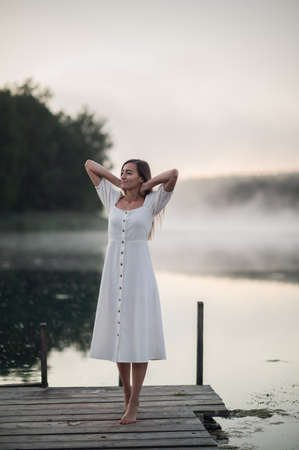 Young woman standing on a wooden pier and breathe deeply on chilly morning with a mist over water. 免版税图像