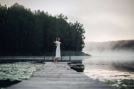 Happy woman in a white dress enjoys morning on a lake. Fog floats over the water. 免版税图像