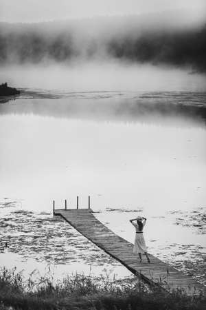 Black and white monochrome picture of young woman in white dress standing alone on footbridge and staring at lake. Foggy chilly morning with a mist over water. 免版税图像