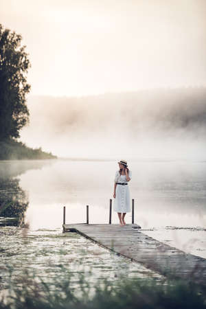 Woman in a white dress and hat standning on a wooden pier with a foggy lake at sunrise.