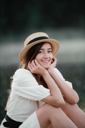 Portrait of a happy caucasian woman in a white dress and hat outdoors sitting and smiling.