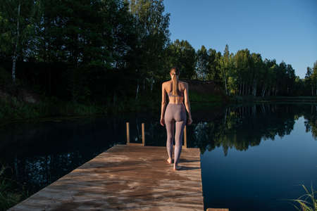 Young woman walks on wooden pier above forest lake scenery, preparing for morning yoga workout in nature.