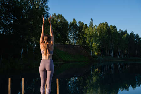 Woman doing yoga on a forest lake. Beautiful girl doing exercises on stretching and flexibility outdoors