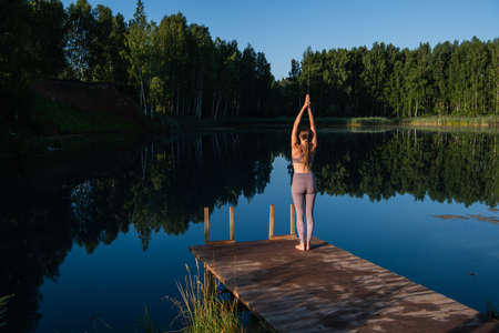Young Woman practicing yoga on the wooden berth at lake. Single sport healthy training on nature at sunny weather
