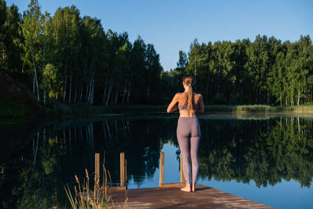 Young woman walks on wooden pier above forest lake scenery, folds her arms in a namaste gesture. Woman arms outstretched in nature.