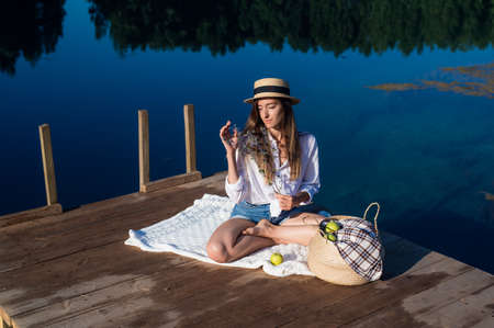 Beautiful young woman wearing blue shorts, shirt and hat enjoys her morning picnic on a wooden pier near the lake.