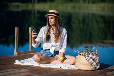 Beautiful young woman in hat has picnic near the lake in summer forest. She eats an apple and looking at smart phone.