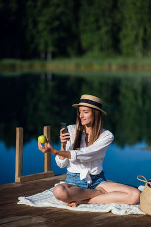 Beautiful happy woman eats an apple and making selfie while sitting on a wooden pier near the lake.