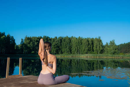 Young female practicing yoga against the sky on a sunrise. Pretty slim woman performs an exercise. Healthcare, meditaion, welness, mindfulness concept.