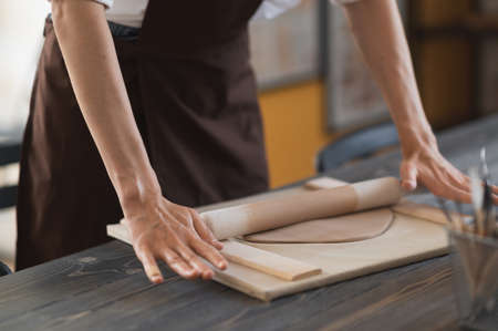 Female hands flatting piece of clay lying on fabric using wooden rolling pin in ceramic studio. Stock fotó