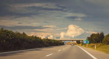 a highway leading to the horizon, a bridge in the distance, in nature, on a background of blue sky with clouds, sunset, Highway D1 / Czech republic 写真素材