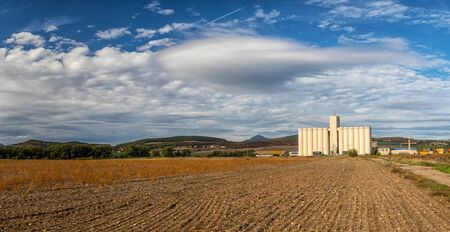 Landscape with field and silo, hills and blue sky with white clouds