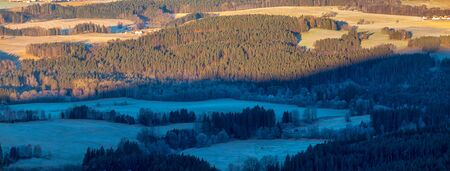 top view of landscape with forests and meadows - half shaded and half lit by sun, shaded trees and meadows with hoarfrost and snow
