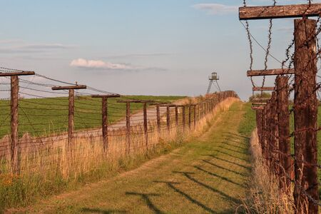 Preserved Iron Curtain Line - barbed wire fence and watchtower on the Czech Republic border, from the Cold War era Archivio Fotografico